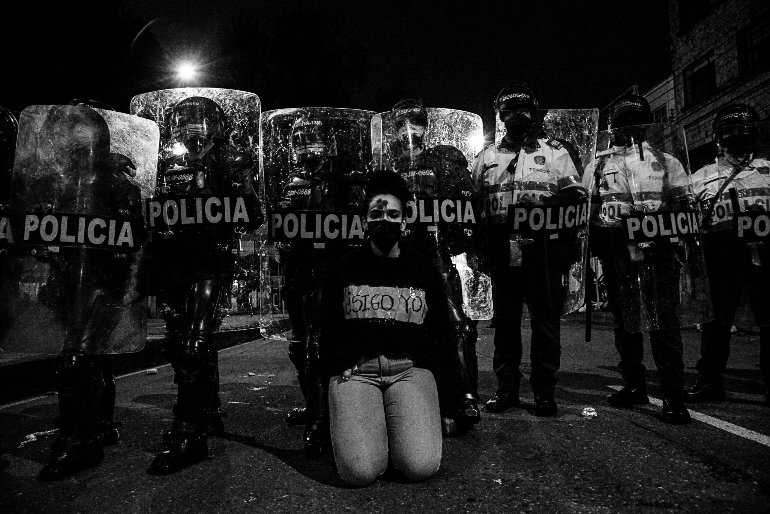 Mujer arrodillada frente a linea de formación de policias
